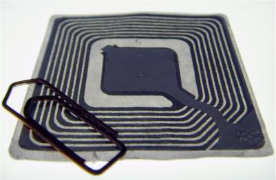 Uma etiqueta de RFID juntamente de um clipe para a comparação de tamanho