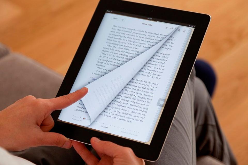 """Pessoa segurando o tablet na mão enquanto vira a """"página"""" de seu livro digital."""