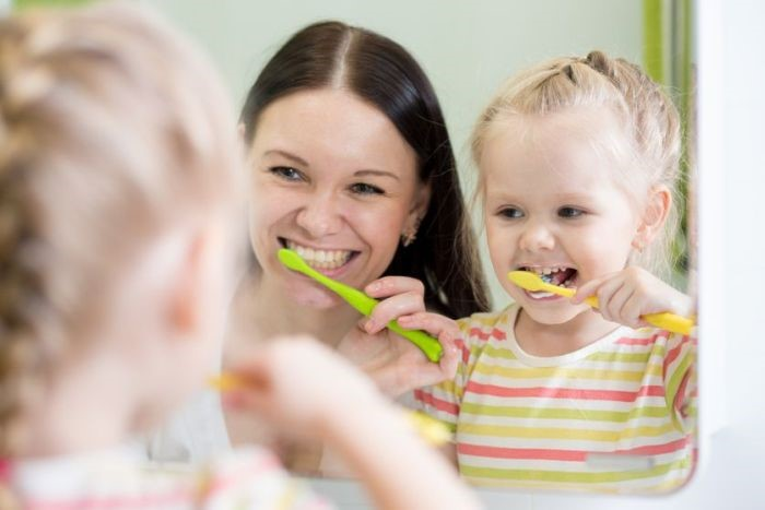 Mãe e filha escovando dentes