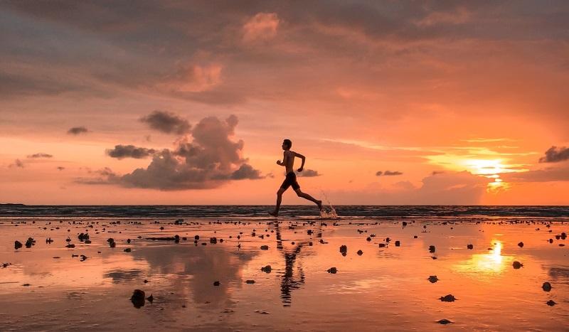 homem correndo em uma praia