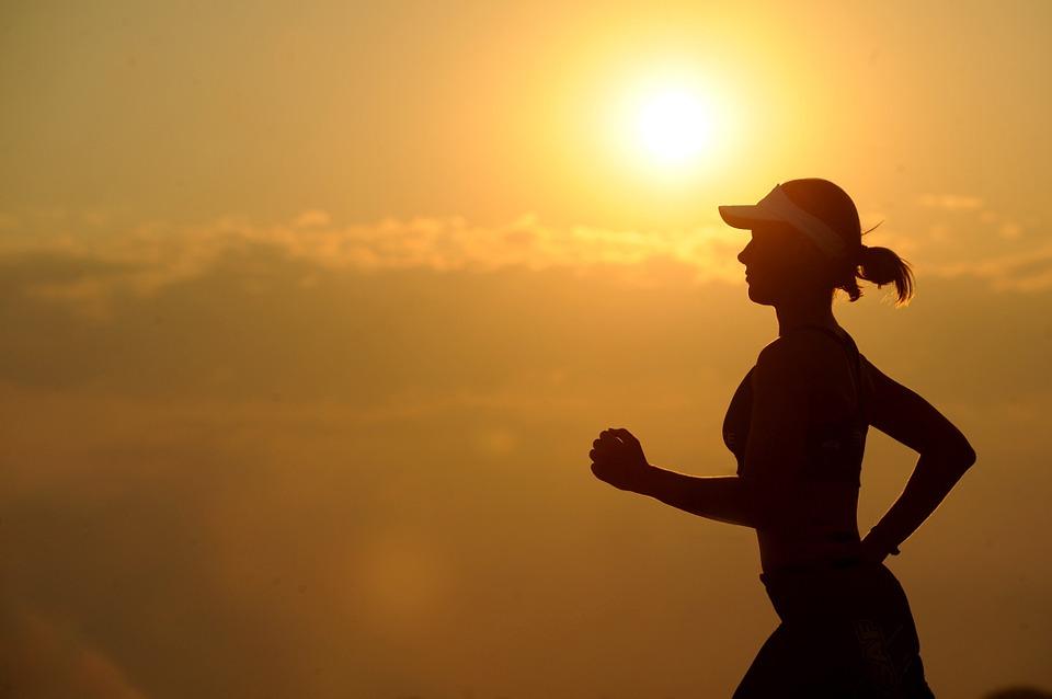 mulher correndo em pôr do sol
