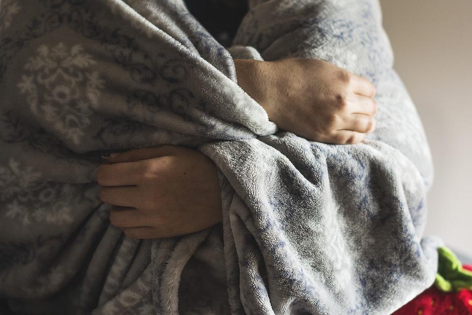 Pessoa enrolada em cobertor