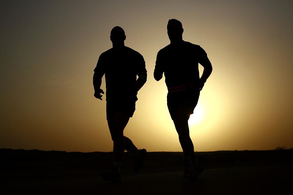Homens correndo em pôr do sol