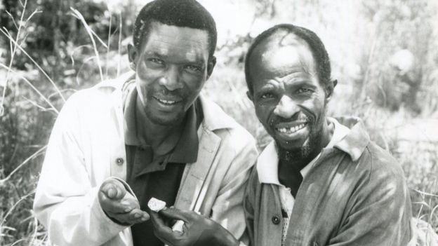 Homens exibindo fóssil