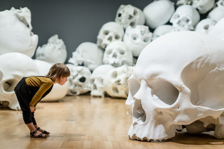 Menina olhando para crânio