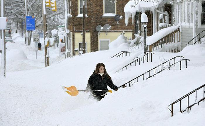 Mulher tirando neve de degraus