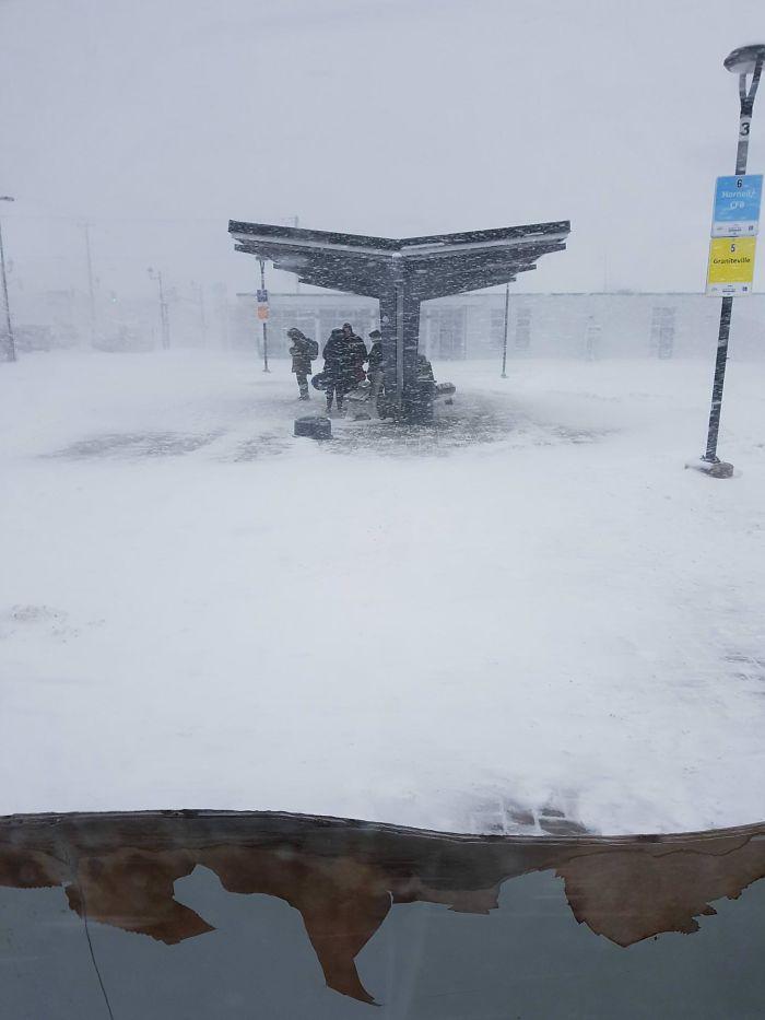 Neve caindo em ponto de ônibus