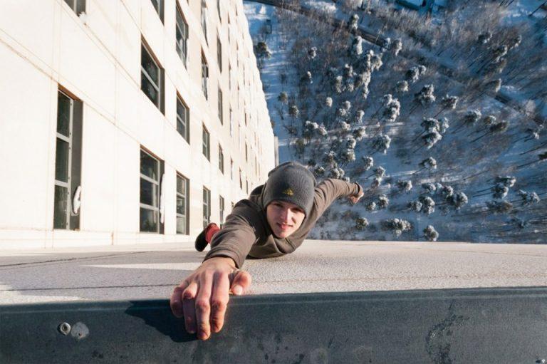 Rapaz pendurado em prédio