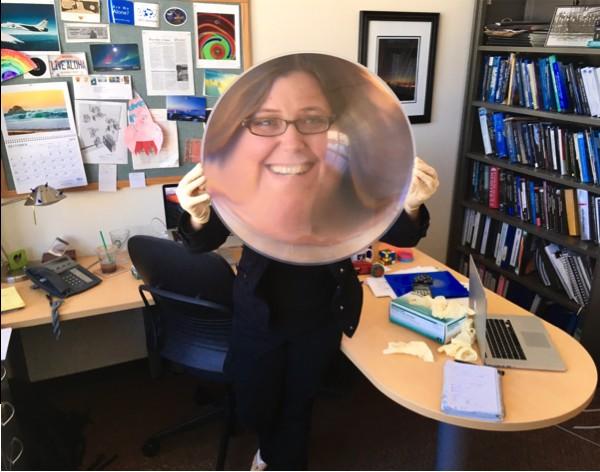 A astrônoma Shelley Wright brinca com revolucionária lente plástica de um dos telescópios do projeto PANISETI.