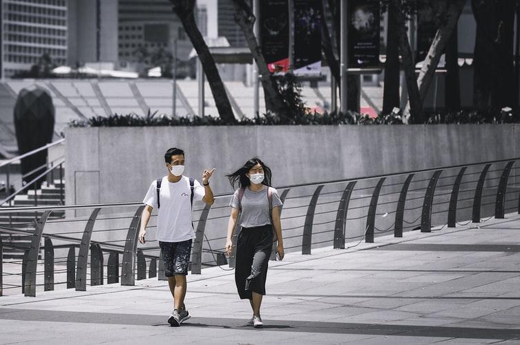 Pessoas andam com suas máscaras de proteção pelas ruas vazias de Singapura, na Ásia. (Fonte: Unsplash)