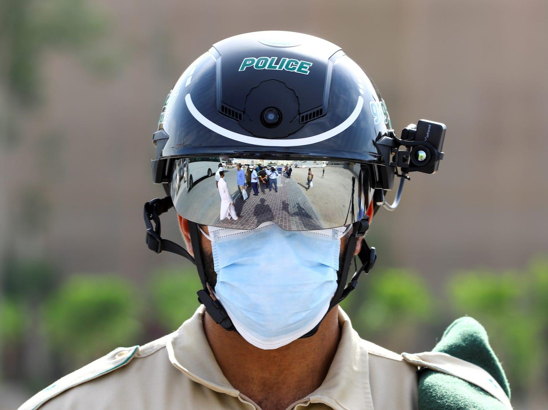 Um policial usa o capacete inteligente para verificar a temperatura de pessoas na rua em 23 de abril de 2020, Dubai