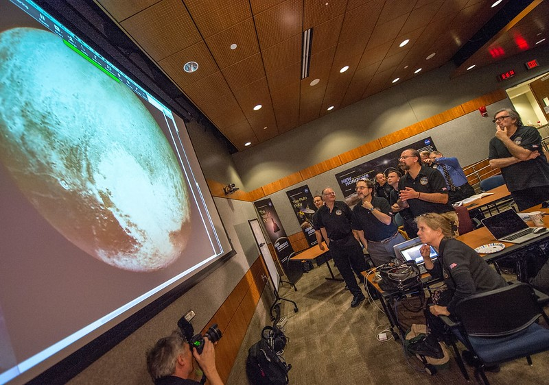 Equipe da NASA em reunião realizada em 2015 analisando as captações de imagens de Plutão (Fonte: NASA/Bill Ingalls)