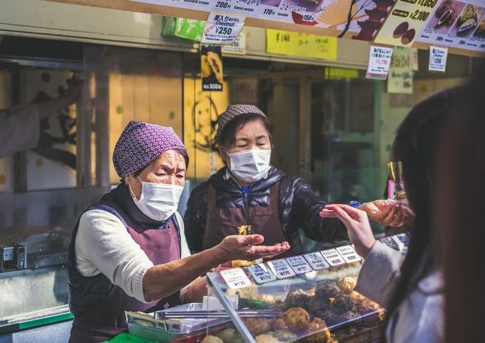 Feirantes usam máscaras de proteção durante a pandemia no Japão. (Unsplash/Reprodução)