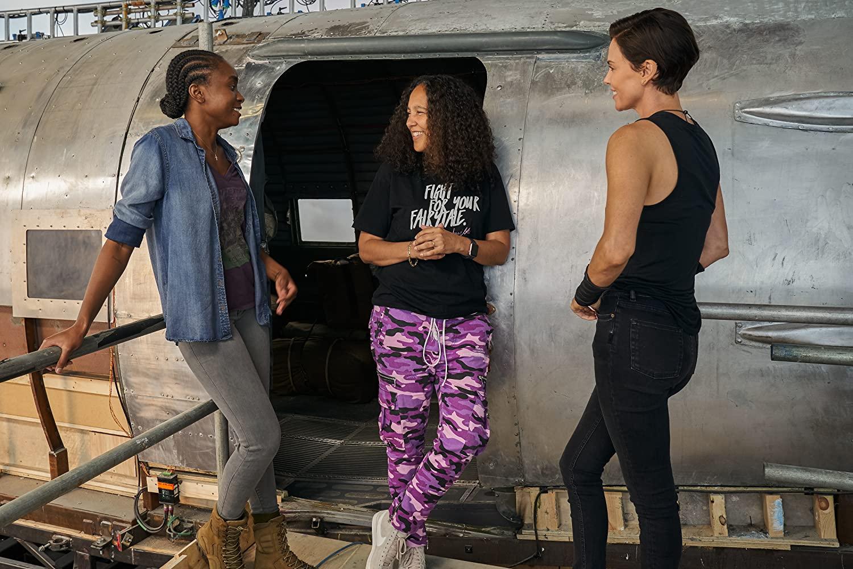 Ao centro, a diretora Gina Prince-Bythewood conversa com as atrizes KiKi Layne e Charlize Theron.