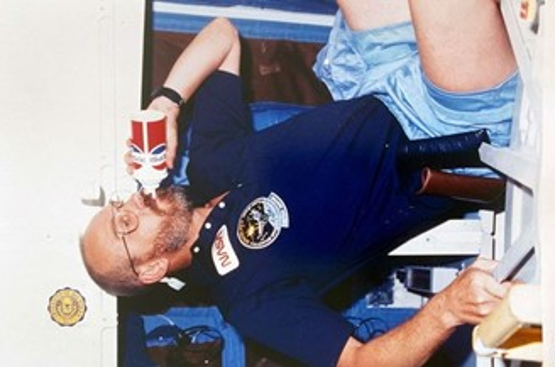 Astronaut Loren Acton experimenting with Pepsi