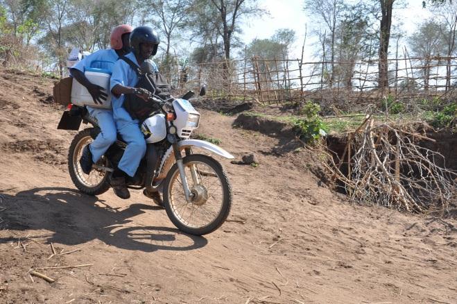 Profissionais de saúde transportam vacinas em coolers para uma aldeia remota a leste do Malawi.