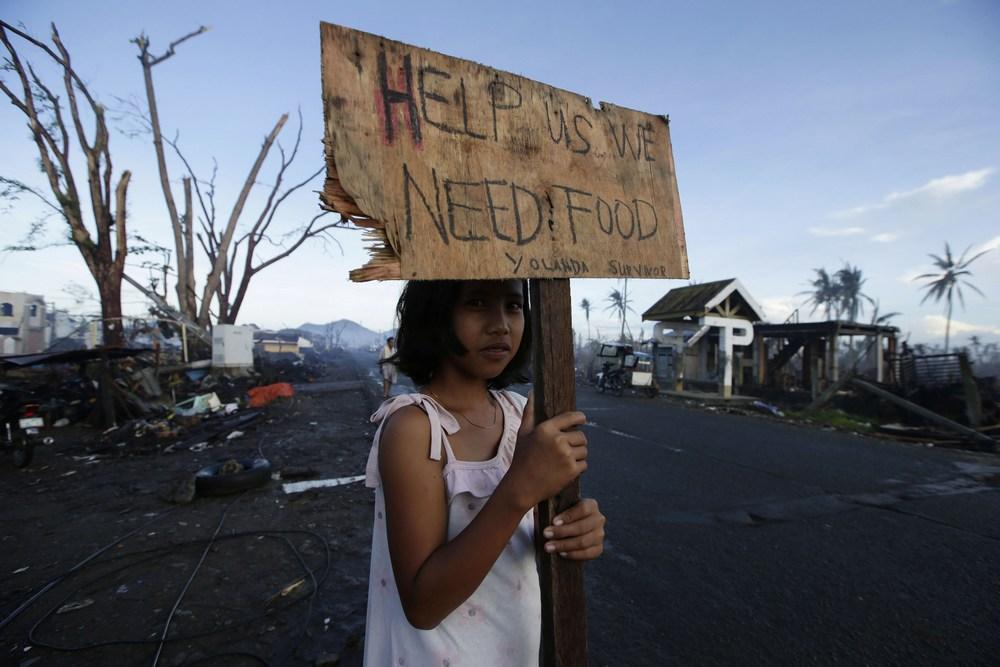 Uma sobrevivente pede ajuda à beira de uma rodovia no município de Palo, nas Filipinas, devastado pelo tufão Yolanda em 2013.