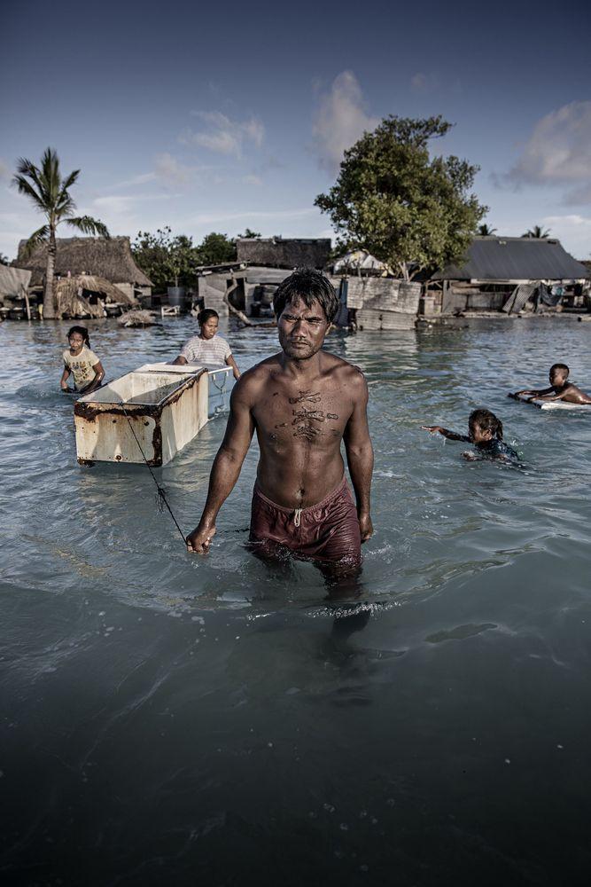 Uma família atravessa sua aldeia inundada, recolhendo pedras para construir um muro de contenção da água do mar em Tarawa, no Kiribati.