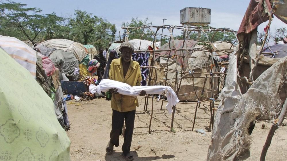 Um homem carrega seu filho morto em um campo de refugiados que acolhe os que escapam da fome, da seca e da guerra em Mogadíscio, na Somália.