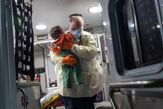 A paramedic carries a 10-month-old baby with suspected covid-19 in Stamford, California.