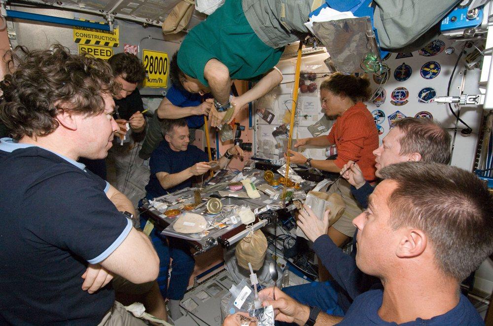 Oito dos 13 tripulantes levados a bordo da ISS pelo ônibus espacial Endeavour se espremem no módulo de refeições.