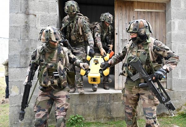 Soldados franceses retiram o robô Spot do campo.