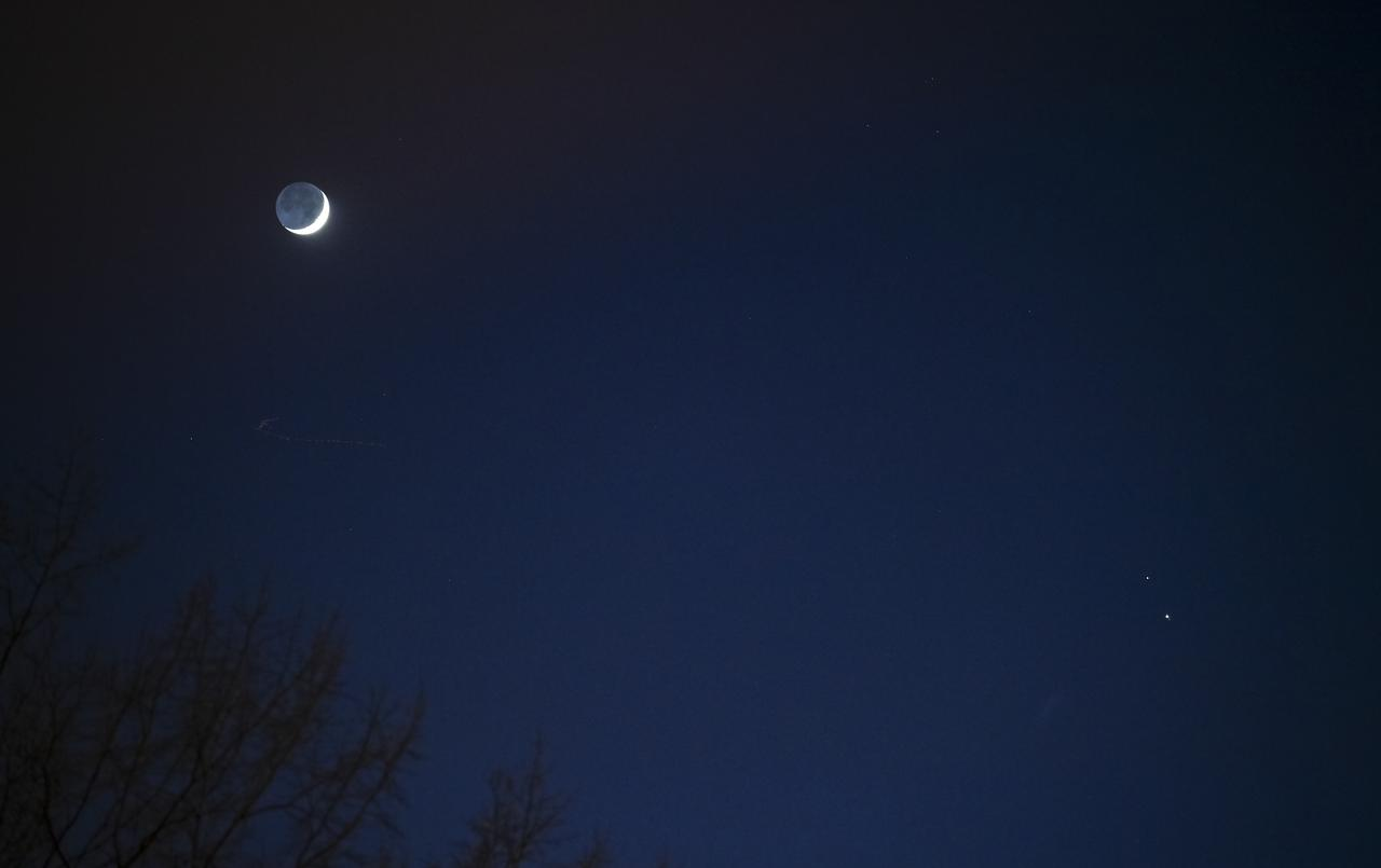 The moon on the left, Saturn above on the right, and Jupiter below, in December 2020.