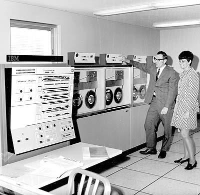 Foto de época mostrando um mainframe com entrada de dados por fitas magnéticas