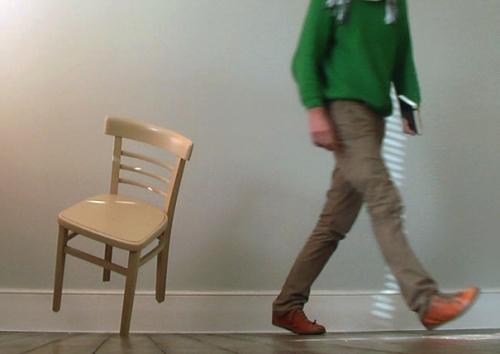 A cadeira apoiada em apenas um pé.