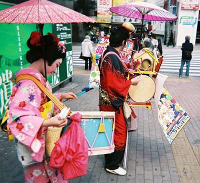 Músicos de rua que fazem propaganda para estabelecimentos comerciais